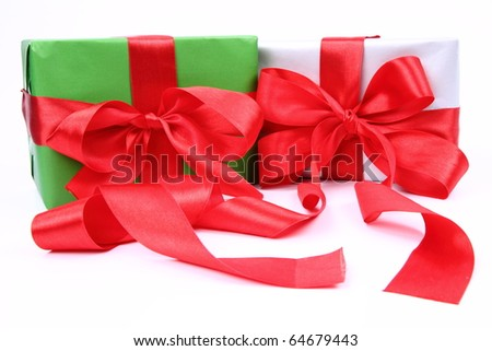 Gifts in green and silver wrapping with red bows on white background