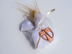 Gifts or favors for the first or holy communion. Isolated small bag of white fabric with ear of wheat and burnished metal Tau Christian cross. Religious symbol