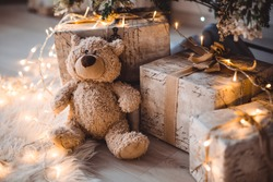 Gifts under the Christmas tree for Christmas. Brown bear soft toy, next to gift boxes in a decorated room. Family tradition, gifts from Santa Claus