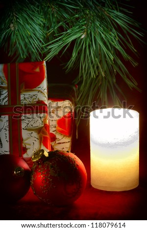 Gifts under the Christmas tree next to a candle