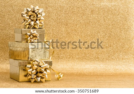 Gifts with ribbon bow on golden background. Holidays decoration #350751689