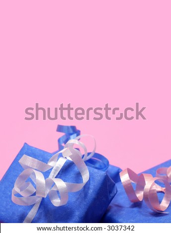 Gifts wrapped in blue with pink, white and blue ribbon on pink background