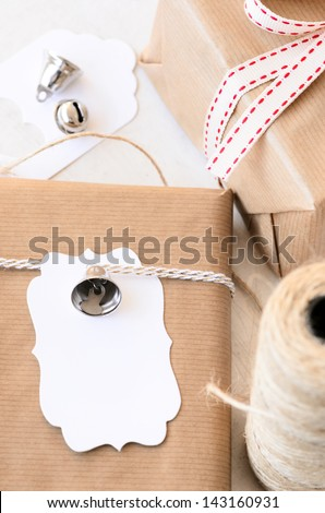 Gifts wrapped in plain paper tied with twine, silver ornaments and a blank gift tag, crafting at home for christmas valentines day