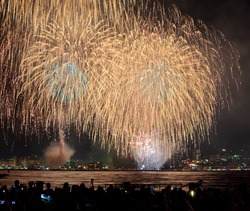 Gigantic, glittering golden fireworks light up the summer sky in Shimonoseki and Kitakyushu, Japan. Huge firework displays are an important tradition in Japan.