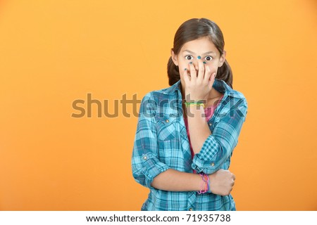 Giggling Latina child on orange background covers her face