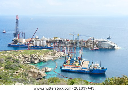 Giglio Island, Tuscany, Italy - April 26 2014: Salvage operation on the wreck of the Costa Concordia ship operated by Titan Salvage company near the harbor