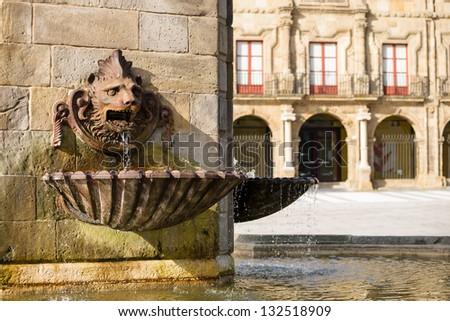 Gijon, Asturias, Spain. Lion fountain of monument to Don Pelayo and Palacio de Revillagigedo on background. Tourist attraction. Plaza Marques.