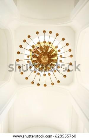 Gilded chandelier against the white ceiling