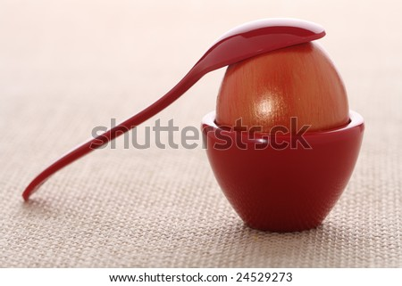gilded red Easter egg in red cup with spoon, on ristic background, shallow DOF