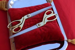 Gilded scissors on red cushion for cutting the ribbon for the opening ceremony. Golden scissors for the ceremonial ribbon-cutting at the opening ceremony on the red cushion and tray with handles.