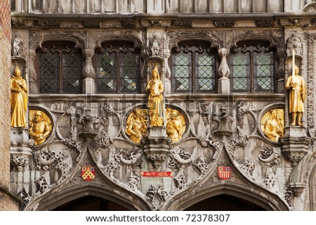 Gilded stone statues decorate the entrance over the doors to the Basilius, or Basilica of the Holy Blood, in Bruges, Belgium. - stock photo