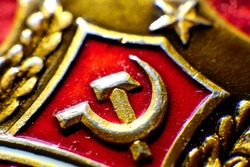 Gilded symbol of communism on a red background.
