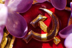 Gilded symbol of communism with a ray of light falling on it on a red background.