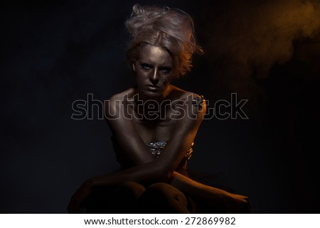 Gilt. Golden Plated Woman\'s Face. Art concept. Gilded Body. Focus on her hands