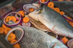 Gilthead bream (Sparus aurata) fish with carrots, lemon and onion prepared to be put in the oven