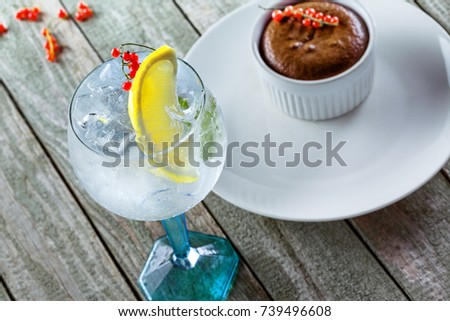 Gin and tonic cocktail with sweet chocolate mousse a wooden table. Alcoholic drinks in a glass with dessert. #739496608