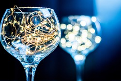 Gin glass with fairy light inside with another one blurred in the background with blue glow, bright lights in a shiny glass against black backdrop, moody and stylish concept