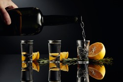 Gin is poured in a small glass from an antique bottle of dark glass. A strong alcoholic drink with lemon and rosemary on a black reflective background.