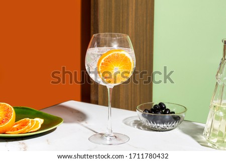 Gin tonic cocktail, garnished with orange slice, colorful background Foto stock ©