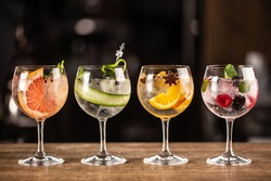 Gin tonic long drink as a classic cocktail in various forms with garnish in individual glasses such as orange, grapefruit, cucumber or berries.