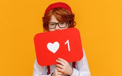 Ginger boy in trendy outfit covering face with board with like symbol and looking at camera while advertising social media against yellow background