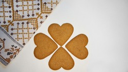 ginger cookies in the shape of heart on a white background, beside folded colored napkin