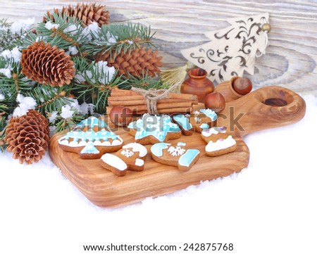 Ginger cookies on a board and fir-tree branches with cones on a white background. Christmas background.