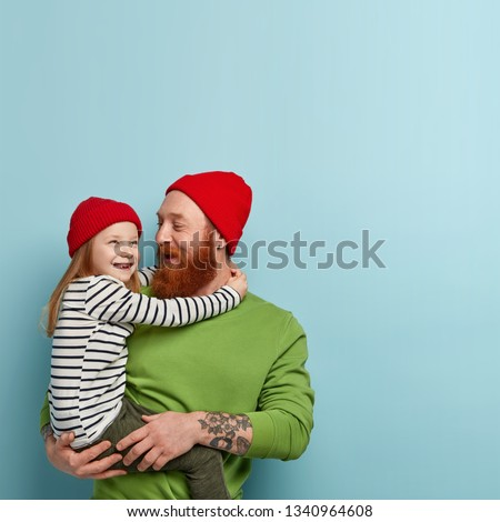 Ginger family have fun. Joyful foxy bearded young man happy to meet daughter after school, share impressions of day, wear similar red hats. Cute smiling dreamy girl embraces father with big love