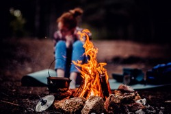 Ginger girl in checkered shirt and denim jeans sitting in front of fire in forest. Human and nature. Traveler girl alone on mountain. Feeling freedom in camp. Sad alone girl.
