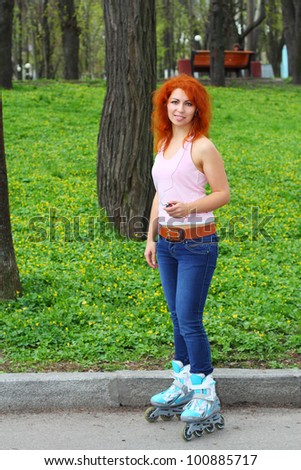 Ginger girl on roller skates listening to music in the park