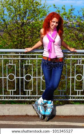 Ginger girl on roller skates with her legs crossed in Mariinsky Park, Kiev
