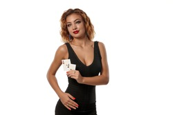 Ginger girl wearing a black dress is posing holding two playing cards in her hands standing isolated on white background. Casino, poker. Close-up.