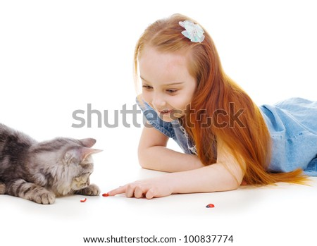 Ginger girl with a cat play with lady-beetle
