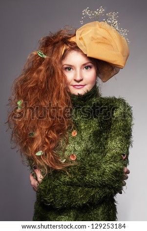 ginger lady with yellow hat and flowers on her head looking at camera