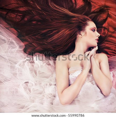 Ginger long haired young woman in sensual pose