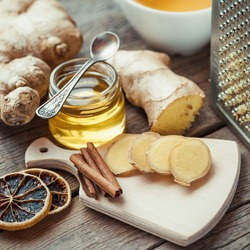 Ginger on cutting board, jar of honey, dried lemon slice, cinnamon and grater on kitchen table. Selective focus.