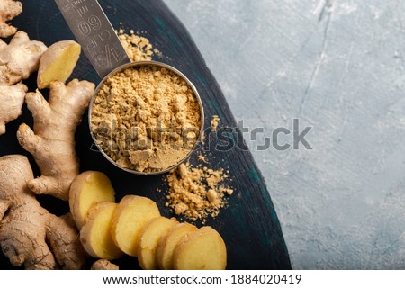 Ginger root and ginger powder in the bowl. Fresh ginger root and ground ginger spice. Photo stock ©