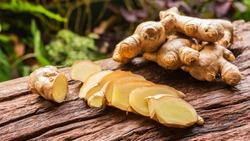 Ginger root and sliced on old plank with nature background. Close-up, Selective focus