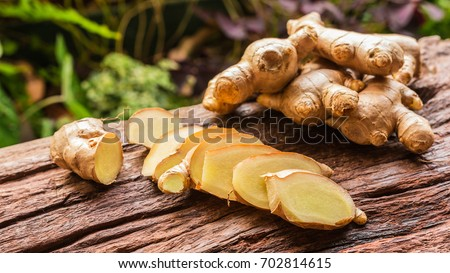 Ginger root and sliced on old plank with nature background. Close-up, Selective focus Foto d'archivio ©