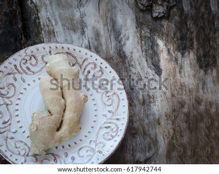 Ginger root on a vintage plate on a background of weathered wood #617942744