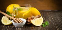 Ginger tea and ingredients - lemon, cinnamon, honey, rustic background