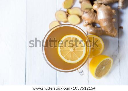 Ginger tea on white table with lemon #1039512154