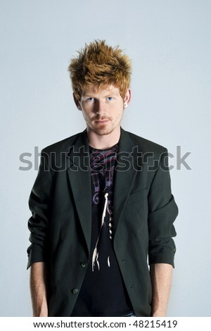 Ginger with bright blue eyes stands looking at camera