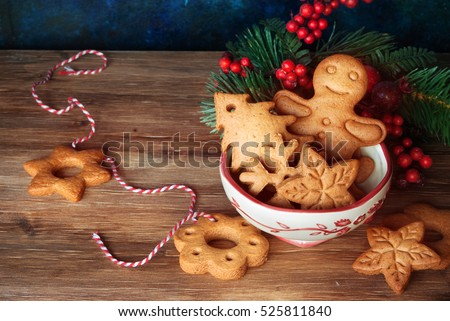 Gingerbread and christmas cookies in a bowl and festive decor on wooden background with a place for text