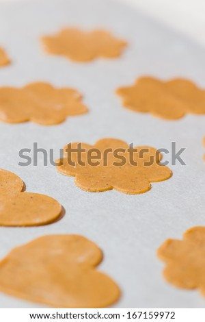 Gingerbread are ready to oven, white parchment below, vertical format