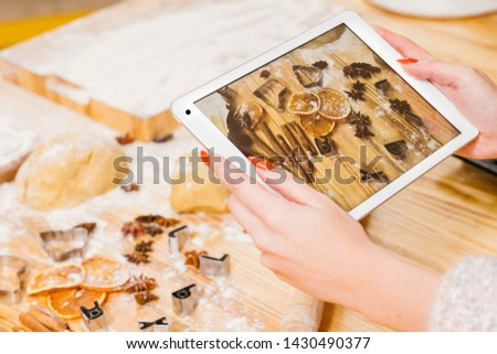 Gingerbread biscuit recipe. Lady using tablet to take picture of pastry ingredients.