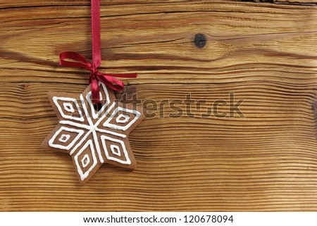 Gingerbread cookie hanging on wooden background. Christmas decoration.