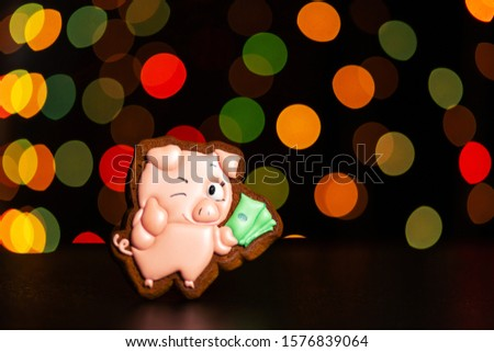 gingerbread cookie of funny pink pig from meme hold money over defocused colored lights of garland. Traditional Christmas food. Christmas and New Year holiday concept #1576839064