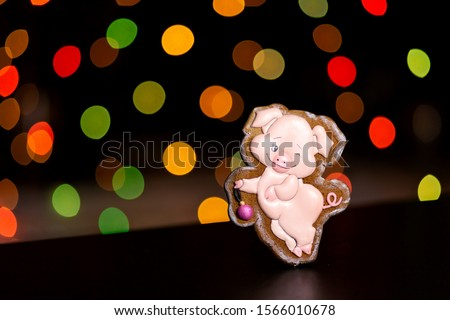gingerbread cookie of funny pink pig over defocused colored lights of garland. Traditional Christmas food. Christmas and New Year holiday concept #1566010678
