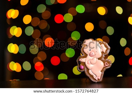 gingerbread cookie of funny pink pig over defocused colored lights of garland. Traditional Christmas food. Christmas and New Year holiday concept #1572764827